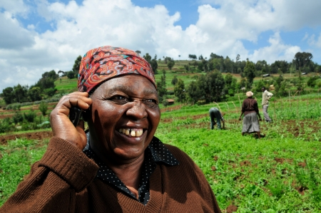 A Kenyan farmer uses a mobile phone in the field_Neil Palmer, CIAT, Flickr CC_ORIGINAL.jpg